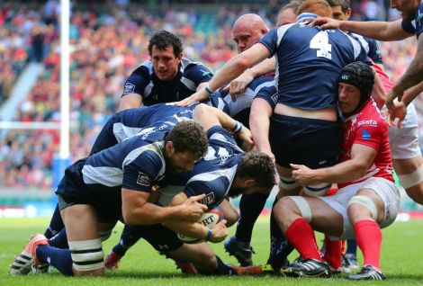 Ben Priddey is helped over the line by his Navy team mates.